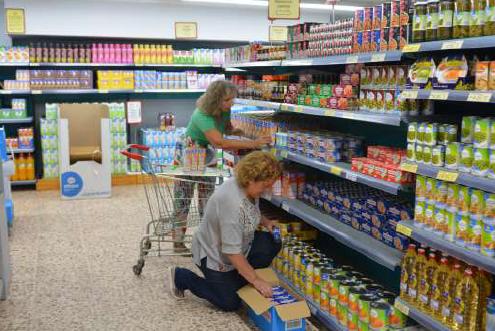 Voluntarias reponiendo productos en el supermercado del economato.